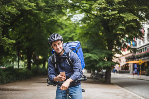 Portrait of confident food delivery man with bicycle in city - MASF15278