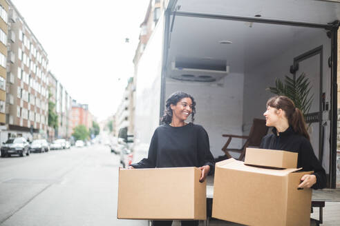 Smiling female movers unloading boxes from truck on street in city - MASF15281
