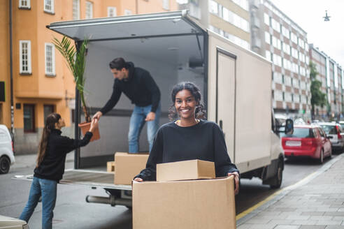 Portrait of confident female mover carrying cardboard boxes - MASF15311