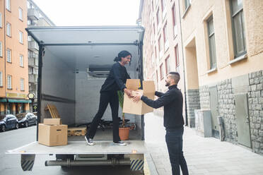 Smiling male and female movers unloading box from truck on street in city - MASF15314