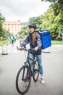 Portrait of confident food delivery woman with bicycle on street in city - MASF15332