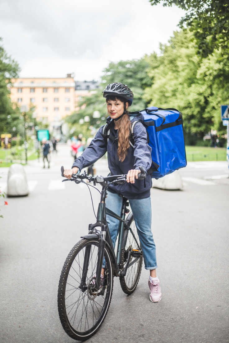 Portrait of confident food delivery woman with bicycle on street in city - MASF15332 - Maskot/Westend61