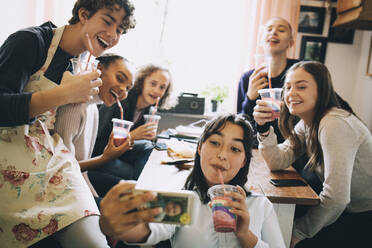 Teenage girl taking selfie with friends through mobile phone while enjoying smoothie at home - MASF15467