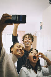 Cheerful friends taking selfie while eating at home - MASF15473
