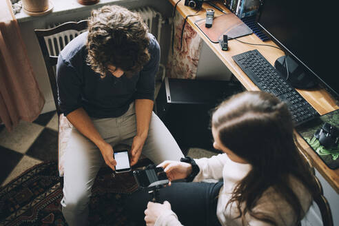 High angle view of teenage friends using smart phone at home - MASF15485