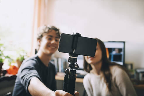 Teenage friends taking selfie with smart phone on monopod while sitting at home - MASF15491