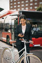 Smiling businesswoman using smart phone while standing with bicycle against bus on street in city - MASF15506