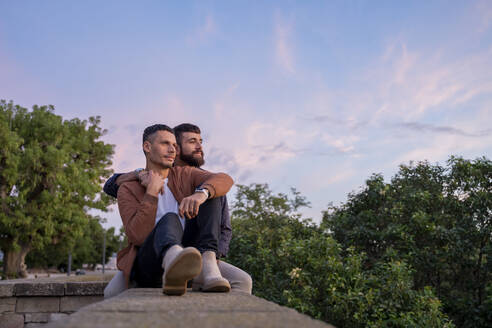 Affectionate gay couple sitting on a wall at sunset - AFVF04421