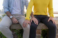 Close-up of affectionate gay couple sitting on a wall - AFVF04445
