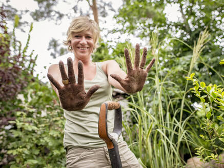 Woman showing her dirty hands in garden - BFRF02142