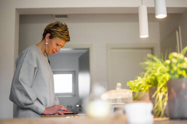 Woman using smartphone in kitchen at home - BFRF02145