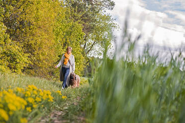 Woman going walkies with dog at a field - BFRF02151