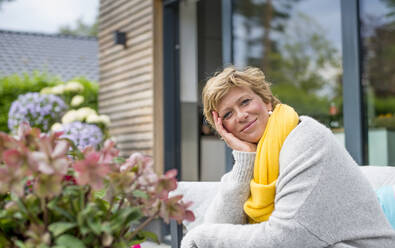 Portrait of smiling woman relaxing on terrace at home - BFRF02154