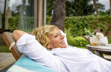 Woman relaxing in deckchair on terrace at home - BFRF02160