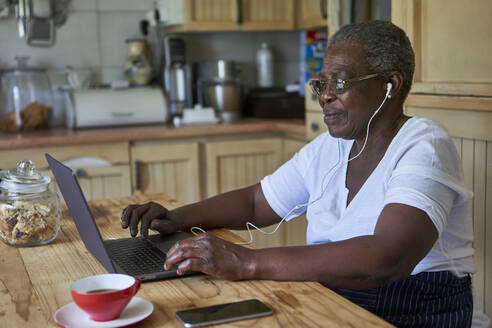 Senior woman sitting at kitchen table using laptop - VEGF01079