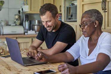 Senior woman and smiling man sitting at kitchen table sharing laptop - VEGF01088