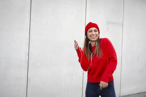 Woman wearing red pullover and wolly hat and dancing in front of a wall - HMEF00693