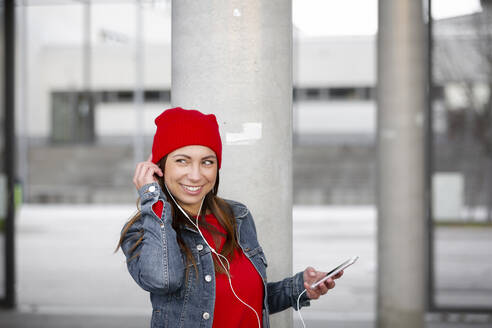 Woman wearing red pullover and wolly hat and listening music - HMEF00696