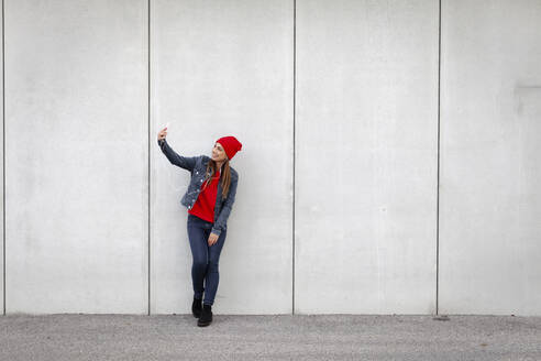 Woman wearing red pullover and wolly hat and taking a selfie in front of a wall - HMEF00699