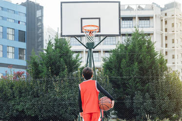 Boy standing with basketball on outdoor court - JCMF00335