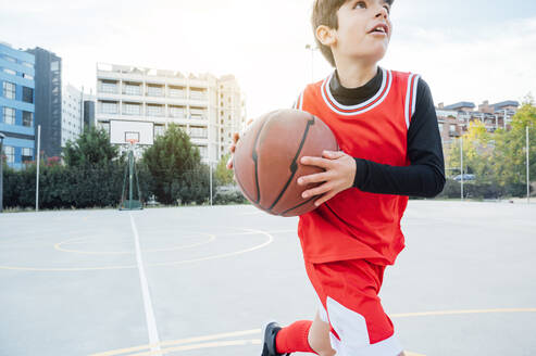 Boy playing basketball on outdoor court - JCMF00338