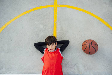 Portrait of boy lying with basketball on outdoor court - JCMF00341