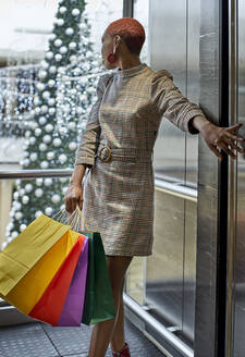 Woman with colorful shopping bags at the elevator with a Christmas tree in the background - VEGF01145