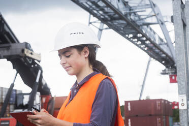 Female worker with clipboard taking notes on industrial site - SGF02499