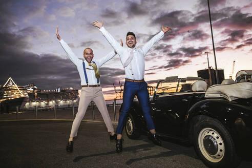 Elegant gay couple jumping at a vintage convertible car at sunset - LJF01127