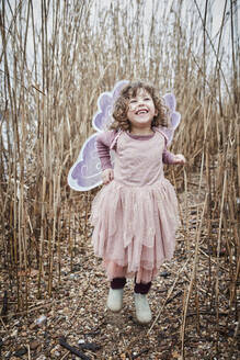 Portrait of happy little girl in nature  dressed up as a butterfly - RORF01969