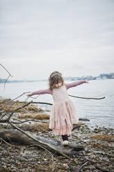 Little girl wearing pink fancy dress costume balancing on deadwood at riverside - RORF01972