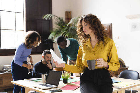 Woman with paper and coffee cup in office with colleagues in background - FMOF00815