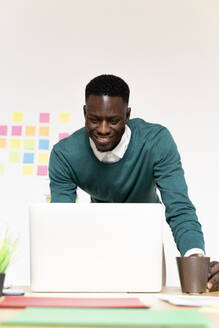 Smiling man working on laptop at desk in office - FMOF00833