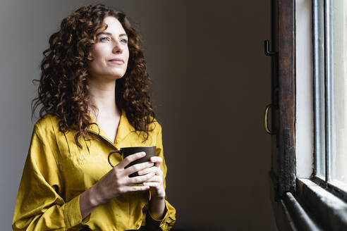 Woman looking out of window with coffee cup - FMOF00839