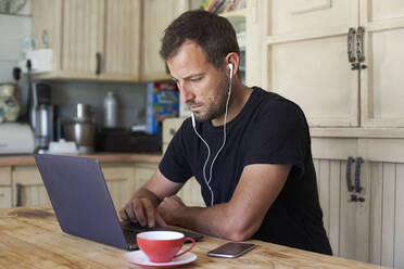 Man working from home, sitting at kitchen table, using laptop and smartphone - VEGF01212