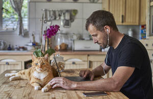 Man working from home, sitting at kitchen table with cat, using laptop - VEGF01221