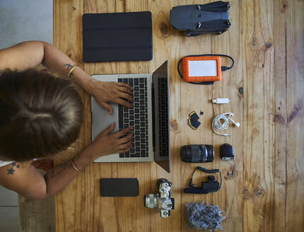 Person sitting at table with photografic equipment, using laptop, overhead view - VEGF01224
