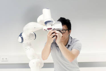 Sudent studying robotic at an university institute, examining robot arm - SGF02505