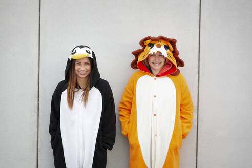 Two women in penguin and lion costume in front of concrete wall - HMEF00707