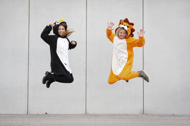 Two women in penguin and lion costume jumping in front of concrete wall - HMEF00710