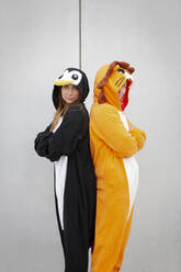 Two women in penguin and lion costume, back to back in front of concrete wall - HMEF00713