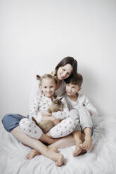Mother with two kids and a cat sitting on bed - EYAF00765