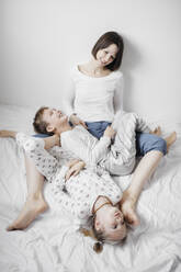 Mother having fun time with two kids on bed - EYAF00768