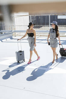 Two fashionable young women with baggage at the airport parking deck - LJF01187