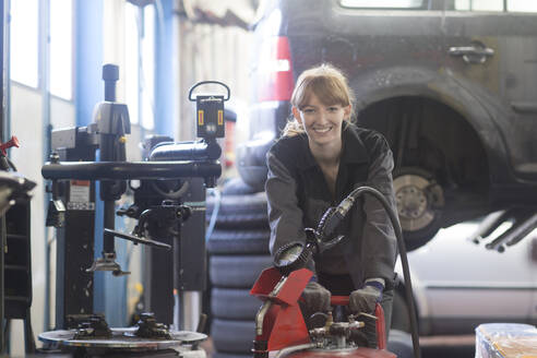 Female car mechanic working in repair garage - SGF02534