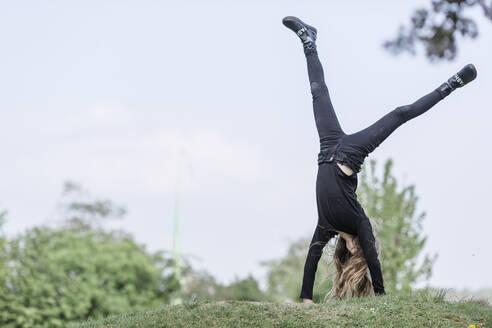 Girl doing a cartwheel on a meadow - STBF00511