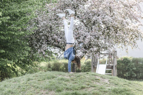 Girl doing a handstand on a meadow - STBF00514