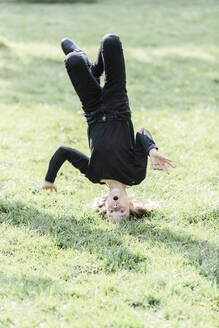 Girl doing a headstand on a meadow - STBF00517