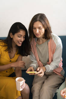 Two women sitting on couch sharing cell phone - AFVF04474
