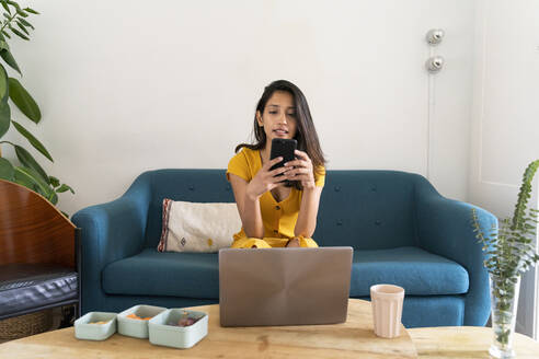 Young woman with laptop sitting on couch using cell phone - AFVF04480